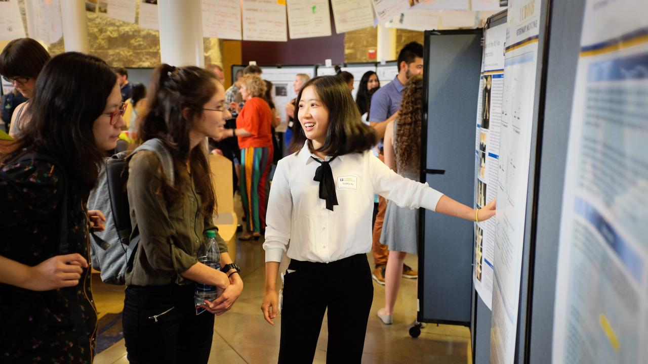 student presents research at a poster session